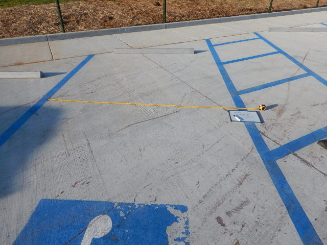 Tape measured being used to measure width of parking spot