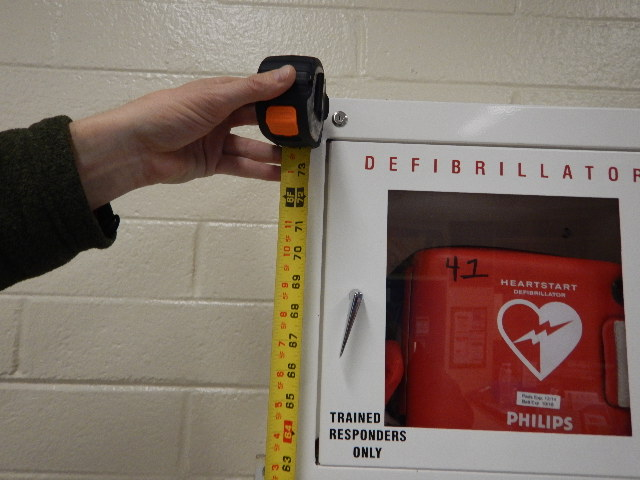 Accessibility specialist measuring height of defibrillator box on wall