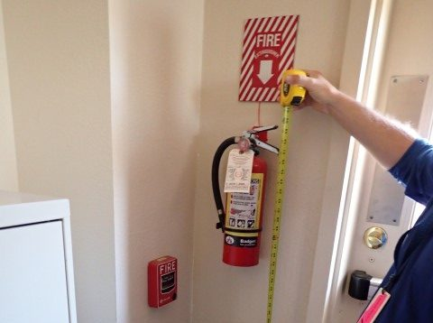 Accessibility specialist measuring the height of a fire extinguisher