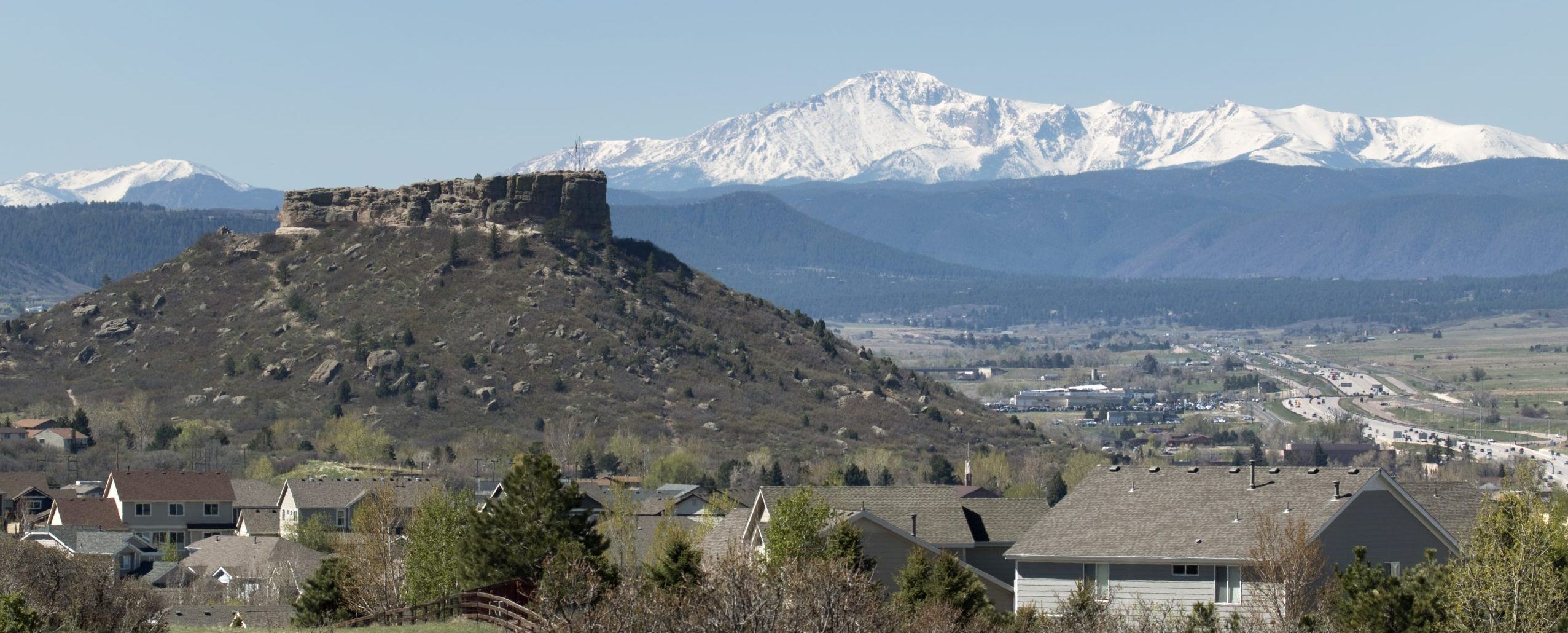 Castle Rock mesa and homes stand in front of a snow covered Pikes Peak with Interstate 25 winding its way to the snowy Rocky Mountains, Castle Rock, Colorado.